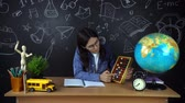 osztály : Portrait of a beautiful schoolgirl student , thinking about choosing a profession, on the background of a black Board with a globe.