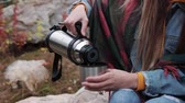 tenda : Tourist drinking tea from a mug of a bottle against the mountains Stock Footage