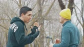 dodge : Boxing workout with trainer outdoors. Young caucasian man in black hoodie practicing punching with personal trainer in the rain. The coach with yellow knit cap teaches dodging