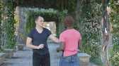 dodge : Self-defense workout with trainer outdoors. Young black man in knitted hat practicing punching with personal trainer in the park. The coach explaining defend combination