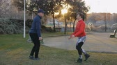 lunge : Workout with personal trainer outdoors. Young attractive woman and fitness instructor doing lunge exercise opposite each other in park at sunset. The coach demonstrating the proper form of exercise Stock Footage