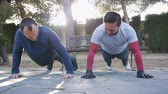 formazione personale : Workout with personal trainer outdoors. Two male athletes doing offset push-ups simultaneously in a park as part of a workout routine. Filmati Stock