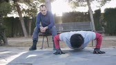 formazione personale : Workout with personal trainer outdoors. Male athlete doing super slow push-ups in a park as part of a workout routine. The coach in military style outfit watches and advices sitting on the bench