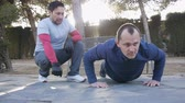 陽気 : Workout with personal trainer outdoors. Fitness man doing super slow push-ups in a park as part of a workout routine. The coach monitors counting the seconds.