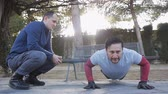 formazione personale : Workout with personal trainer outdoors. Fitness man doing super slow push-ups in a park as part of a workout routine. The coach controls counting the seconds