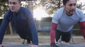 formazione personale : Workout with personal trainer outdoors. Two male athletes doing plank knee to elbow exercises together in a park as part of a workout routine. Slow motion Filmati Stock
