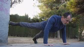 ups : Workout with personal trainer outdoors. Male athlete in military style boots and trousers doing raised leg push-ups in a park as part of a workout routine