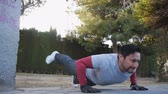 formazione personale : Workout with personal trainer outdoors. Fitness man doing raised leg push-ups in a park as part of a workout routine