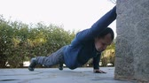 formazione personale : Workout with personal trainer outdoors. Male athlete in military style boots and trousers doing raised arm push-ups in a park as part of a workout routine
