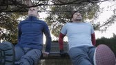 formazione personale : Workout with personal trainer outdoors. Low angle view of two fitness men doing triceps bench dips in a park as part of a workout routine Filmati Stock