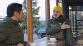 latin american : Two male athletes in warm bubble jackets talk after training in the outdoor area of the cafe in the evening. The guy with yellow knit cap tells something about the workout Stock Footage