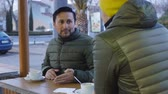 latin american : Two male athletes in warm bubble jackets talk after training in the outdoor area of the cafe in the evening. Man with the beard tells something about the today workout Stock Footage