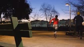 Workout with personal trainer outdoors. Young attractive woman and male fitness coach shuttle racing together between two benches in park after sunset Stockvideo