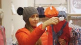 Attractive woman in baby clothes store. Caucasian female in gray knit hat and red jacket takes the baby shirt off the hanger examining it