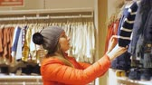 halenka : Attractive woman in baby clothes store. Caucasian female in gray knit hat and red jacket inspecting and touching baby clothes on the hanger Dostupné videozáznamy