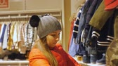 halenka : Attractive woman in baby clothes store. Caucasian female in gray knit hat and red jacket looking at baby clothes on the hanger examining the price tags