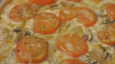 pepperoni pizza : Close-up pan shot of baked pizza with tomatoes and champignons