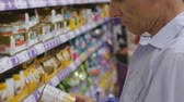 ショッピングカート : Senior man in supermarket. Close-up of elderly gray-haired man in blue shirt picking can of food for animals on store shelves background