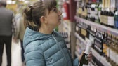 agd : Woman in supermarket. Young caucasian woman in blue jacket reads the label on the small bottle choosing sparkling wine
