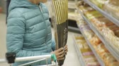 agd : Woman in supermarket. Back view of young caucasian woman in blue jacket choosing bread baguette putting it in the cart