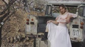 ピックアップ : Woman in blooming garden. Attractive blonde caucasian woman in long white skirt sitting in the back of abandoned pickup truck