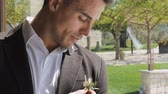 фрак : Close-up of young hispanic muscular man standing by window touching the brooch on his brown jacket.