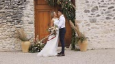 pas getrouwd : Slim blonde caucasian bride and athletic hispanic groom with a bright bouquet in hands looking at each other on wall and wooden door of ancient castle background outdoors. Long shot.