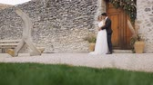 pas getrouwd : Slim blonde caucasian bride and athletic hispanic groom with a bright bouquet in hands kissing looking at each other on wall with wooden door of ancient castle background. Low angle long shot. Stockvideo