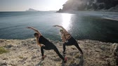 respirar : Two young women doing exercises by the sea. Slim attractive caucasian girls practicing yoga doing stretching exercise on small bay background. Back view. Push in shot. Slow motion.
