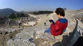 ephesus : bored kid use digital tablet in amphitheather of ancient Ephesus Turkey Stock Footage