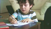 finding : Little boy doing homework
