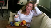 couch : Woman watching tv and eating fruit