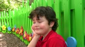 facial : Little Boy Posing Outside by Fence Stock Footage