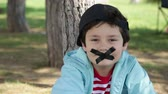 chatty : chatty child covers his mouth with sellotape Stock Footage