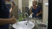 vaidade : woman is standing in front of the bathroom mirror and brushing her teeth