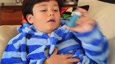 špatně : Young boy  seated on a sofa taking asthma treatment with inhaler Dostupné videozáznamy