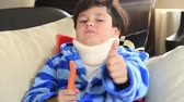 хорошее здоровье : Portrait of a little boy  with a neck brace sitting on a couch  and showing thumbs up