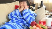 špatně : Portrait of a little boy  with a neck brace sitting on a couch and eating carrot