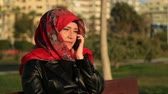 mysterious : Arabic muslim woman wearing red scarf, sitting on a park bench and talking on the cell phone Stock Footage