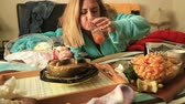 жадность : Portrait of a woman in depression lying on a bed and eating junk food