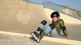 blading : Young boy in frond  of a skating ramp sitting and smiling to camera showing thumbs up