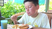 hranolky : Cute boy eating pizza and  french fries at the restaurant