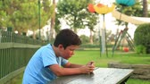 Child relaxing with smartphone in park.