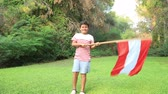 flagstone : Portrait of a young boy holding and waving the Austria  flag at the park Stock Footage