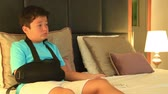 špatně : Portrait of a painful, bored young boy with injured arm watching television in the bedroom
