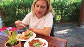 hranolky : Middle aged woman in white shirt and long blond hair eating a fast food at table in restaurant