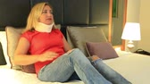 špatně : Painful woman with a neck brace lying on a bed and resting