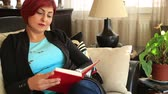 eğlence peşinde : Middle aged, woman with red hair sitting on coach and reading a book Stok Video