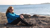 divorce beach : Thoughtful, pensive woman on winter sea beach sitting Stock Footage