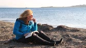 beatitude : Middle aged woman warmly clothed on the beach in autumn, relax and reading book